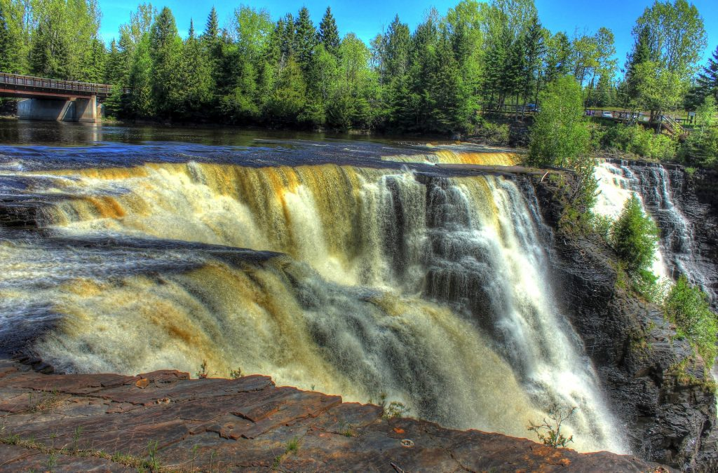 Kakabeka waterfall Canada, on blue sky and green trees background
