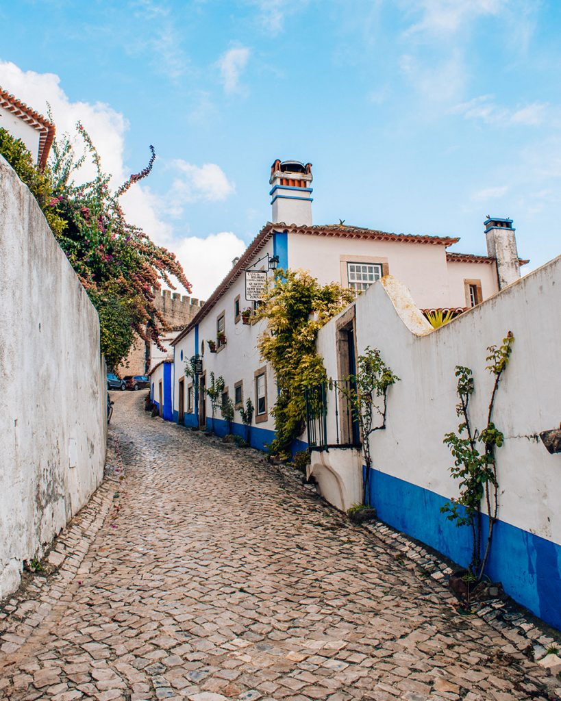 Obidos Portugal quaint street with cobblestone, whitewashed buildings with blue accents, and flowers