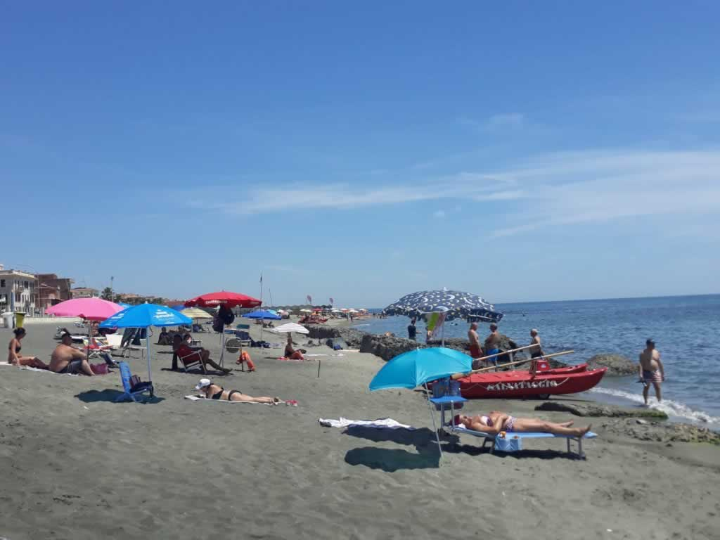 REd boat and people on Lido di Ostia Beach near Rome